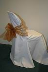 White chair cover with gold bow